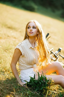 Close-up of a beautiful european woman in casual clothes sitting on a lawn and looking away next to a yellow bicycle on a country walk
