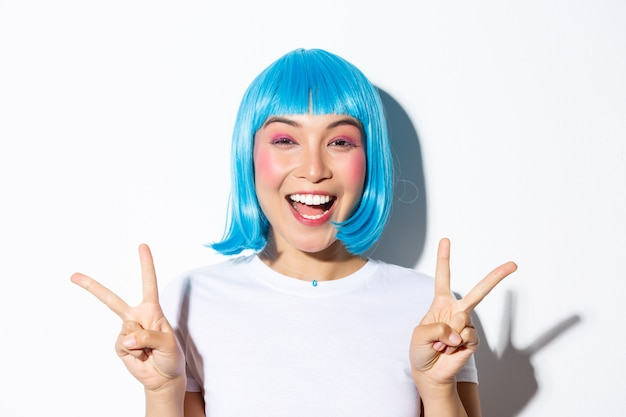 Close-up of beautiful excited asian girl showing peace gesture and smiling