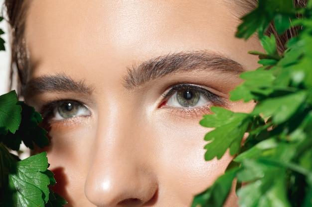 Primo piano di bel viso femminile con trattamento organico su bianco.