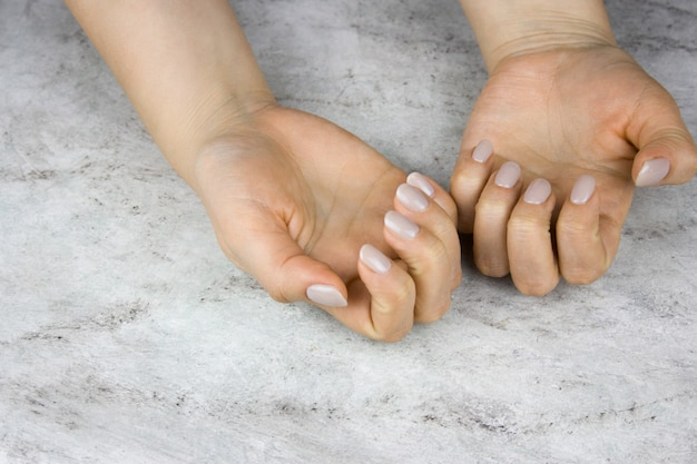 Close up of beautiful female hands with manicure on marble table
