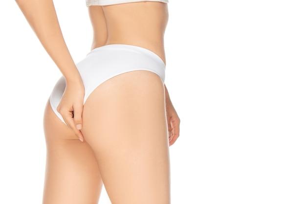 흰색 배경에 고립 된 아름 다운 여성 모델을 닫습니다. 미용, 화장품, 스파, 제모, 다이어트 및 치료, 피트니스 개념. 잘 관리 된 피부를 가진 핏과 스포티하고 관능적 인 바디.