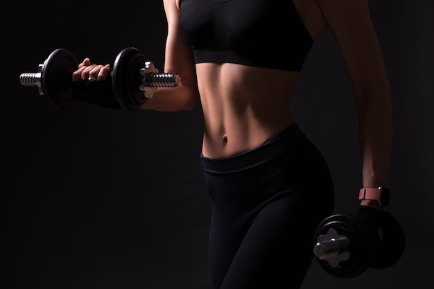 Close up of beautiful female muscular body with dumbbells over black background
