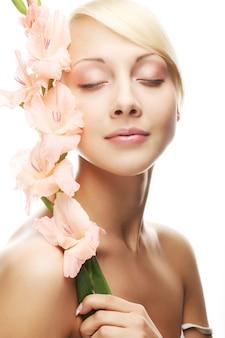 彼女の手にピンクのグラジオラスの花とクローズアップの美しい新鮮な顔