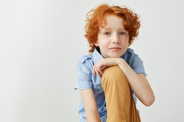 Close up of beautiful ginger boy in blue shirt and yellow jeans holding hand on leg