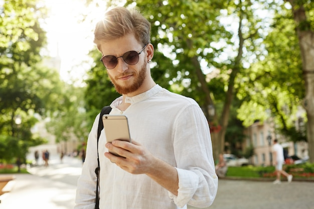 Close up of beautiful ginger male with beard and earring in stylish glasses texting with friend, going home after hard day on work.