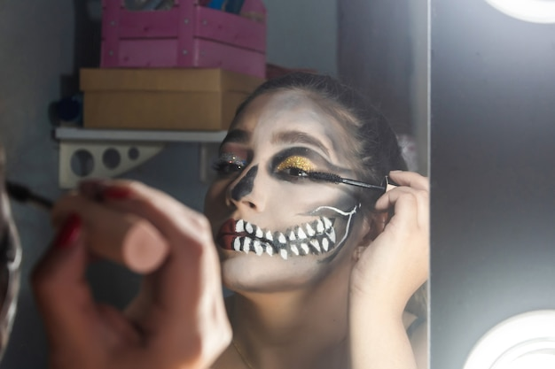 Close-up of a beautiful girl lifting her eyelashes, halloween makeup done in her room.