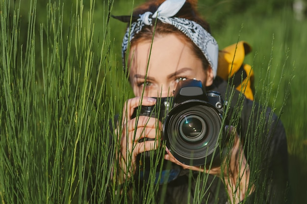 클로즈업, beautiful girl 사진사는 전문 사진-비디오 카메라를 들고 있습니다. 녹색 자연을 배경으로.