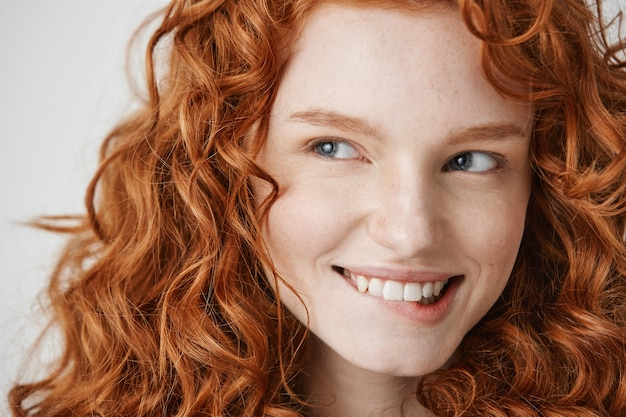 Close up of beautiful girl with curly red hair and freckles smiling biting lip .