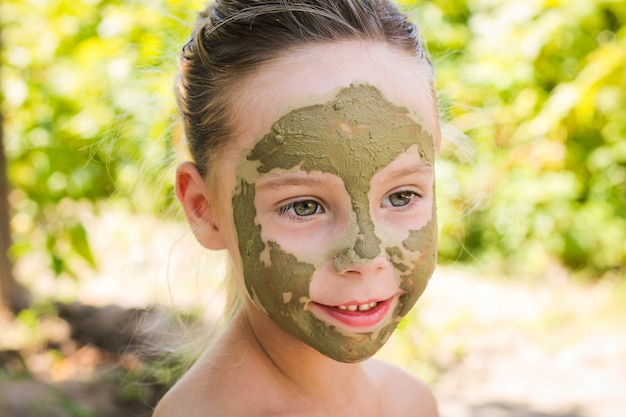 Close up of beautiful girl with facial clay mask