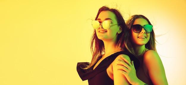 노란색으로 격리된 세련된 수영복과 안경을 쓴 아름다운 소녀들을 클로즈업