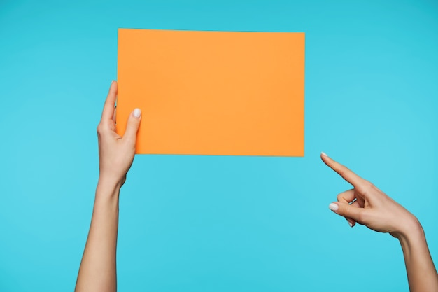 Close up on beautiful hands holding blank sheet of paper Free Photo