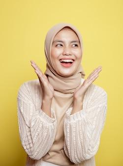 黄色の背景に分離された非常に興奮した美しいヒジャーブの女性の拍手笑顔の表現をクローズアップ