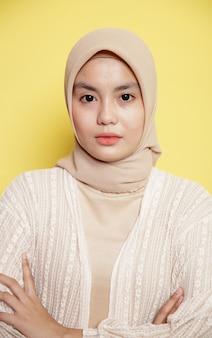 Крупным планом красивые женщины в хиджабе скрестили руки, глядя в камеру, изолированные на желтом фоне