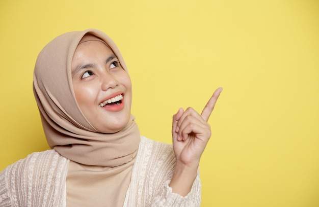 Крупным планом красивые женщины в хиджабе улыбаются, счастливы, у них есть что-то хорошее, указывая на пустое пространство, изолированное на желтом фоне