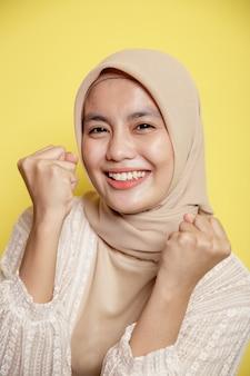 Крупным планом красивое выражение улыбки женщины в хиджабе, очень взволнованное, глядя в камеру, изолированную на желтом фоне