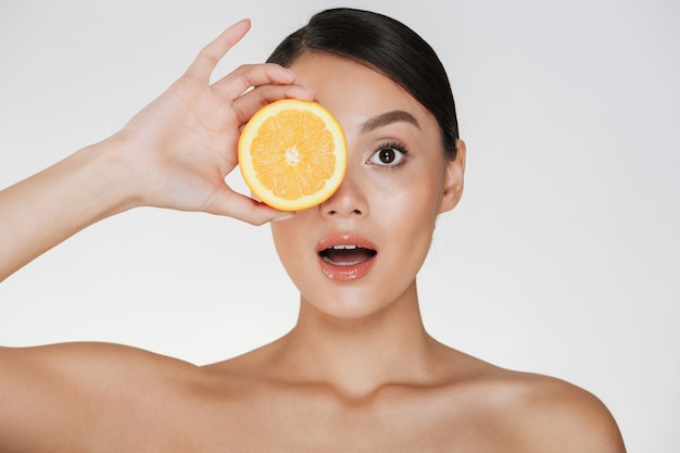 Close up of beautiful lady with soft fresh skin holding juicy orange, enjoying natural vitamin isolated over white