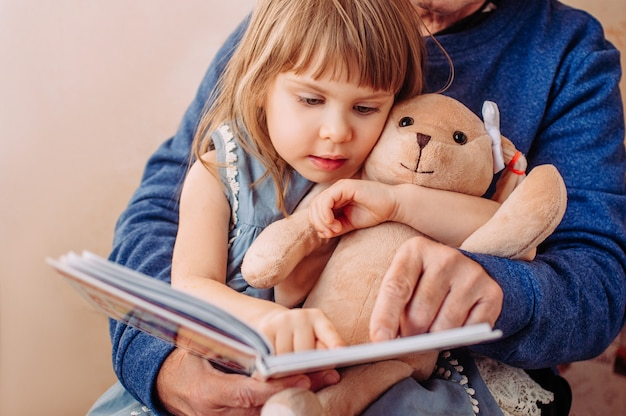 Close up of beautiful little girl reading book with her grandfather