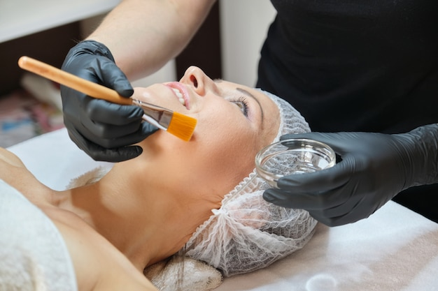 Close up of beautiful mature woman lying on procedure in spa salon