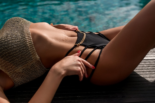 Close up: beautiful model body in a black and gold bikini relaxes near the pool