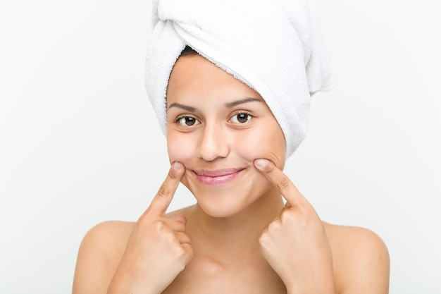 Close up of a beautiful and natural hispanic young woman with a towel on her head