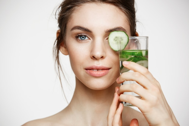 Close up of beautiful nude girl smiling looking at camera holding glass of water with cucumber slices over white background. healthy nutrition. beauty and skincare.