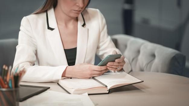 Закройте вверх красивого офисного работника в белой куртке, делая заметки в своем журнале, держа смартфон или телефон в руках, сидя перед журналом.