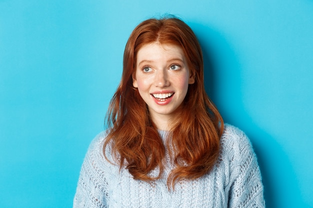 Close-up of beautiful redhead girl in sweater, looking at upper left corner promo logo and smiling, standing over blue background.