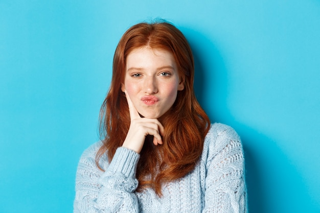 Close-up of beautiful redhead girl thinking, pucker lips and staring thoughtfula t camera, making choice, standing over blue background.
