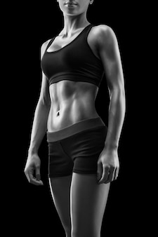 Close up of beautiful sexy female slim tanned body. cheerful attractive young fitness woman in black top and black leggings isolated over white background. black and white photo.