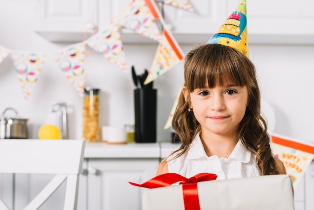 Close-up of beautiful smiling birthday girl holding gift box in the kitchen