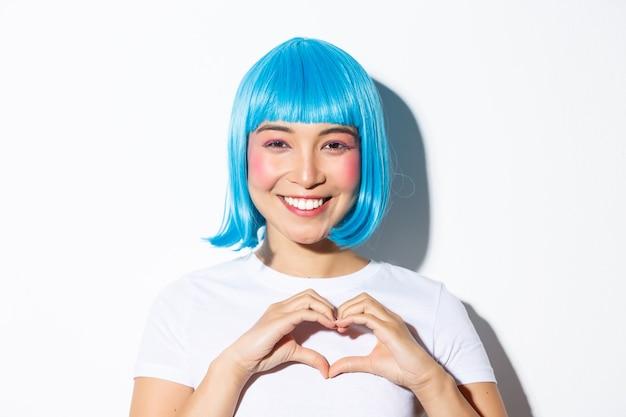 Primo piano di bella donna sorridente in parrucca blu, celebrando halloween, mostrando il gesto del cuore, in piedi.