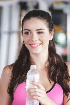 체육관에서 미네랄 워터 한 병을 들고 웃는 아름다운 스포티 한 여자를 닫습니다