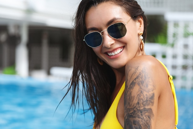 Close-up of beautiful tanned woman with tattoo in yellow bikini, smiling camera near swimming pool.