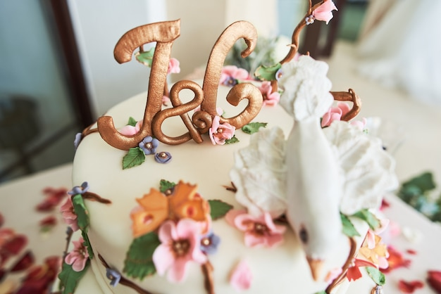 Close-up of a beautiful wedding cake with decorative flowers.