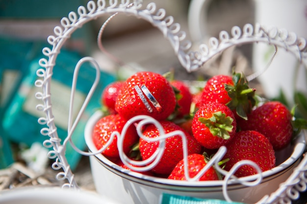 Close-up of beautiful wedding rings protrude from strawberries in a vase with a strawberry slide, selective focus