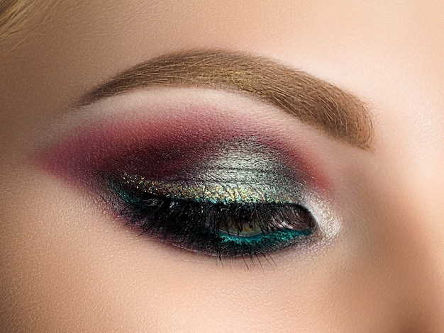 Close up of beautiful woman eye with multicolored smokey eyes makeup