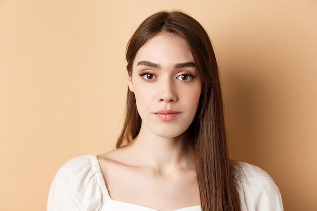 Close up of beautiful woman face with natural makeup and relaxed expression standing on beige backgr...