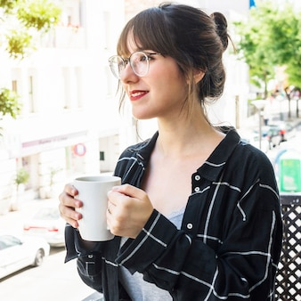 Close-up of a beautiful woman holding cup of coffee