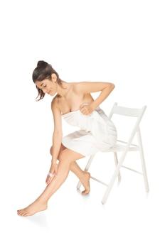 白い背景の美容化粧品スパ脱毛で隔離の下着で美しい女性をクローズアップ