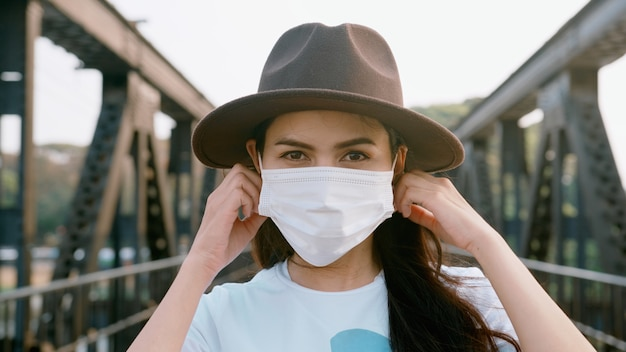 Close up beautiful woman is wearing surgical mask on the bridge