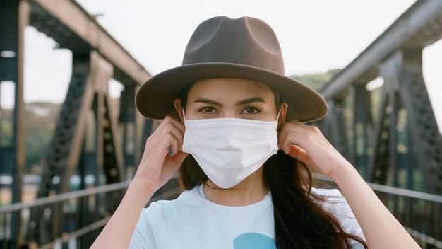 クローズアップ美しい女性が橋にサージカルマスクを着用しています