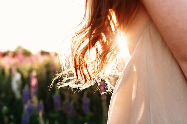 Close up of beautiful woman lock of hair on sunset background in flower field.
