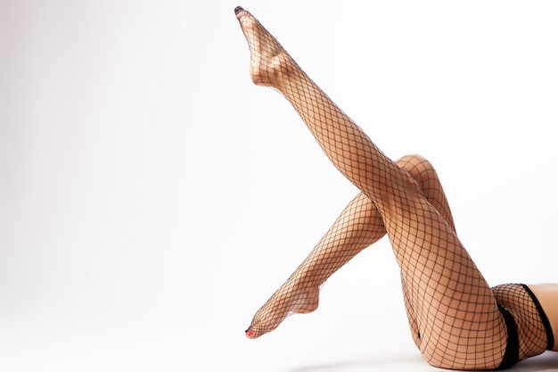 Close-up of beautiful woman's slim legs in nylon black tights in a mesh posing on white isolated.