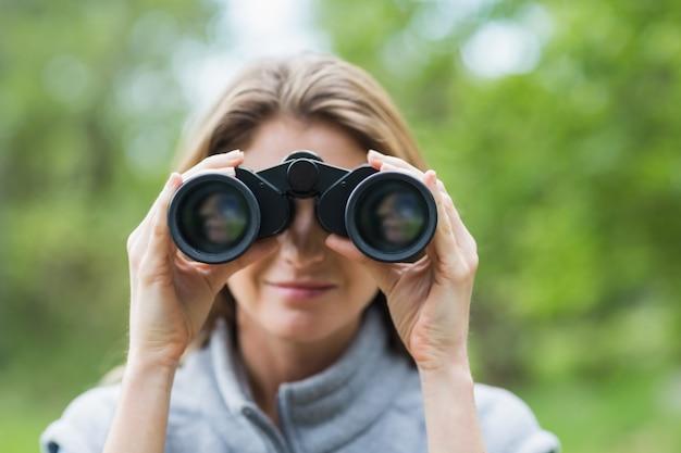 Close-up of beautiful woman with binocular