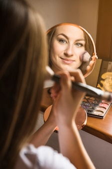 Close-up of a beautiful woman with hand mirror applying blusher on her face