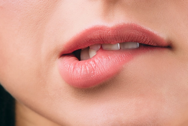Close up of beautiful women's lips covered with lipstick. bite lower lip. white teeth. sexy move. cut view