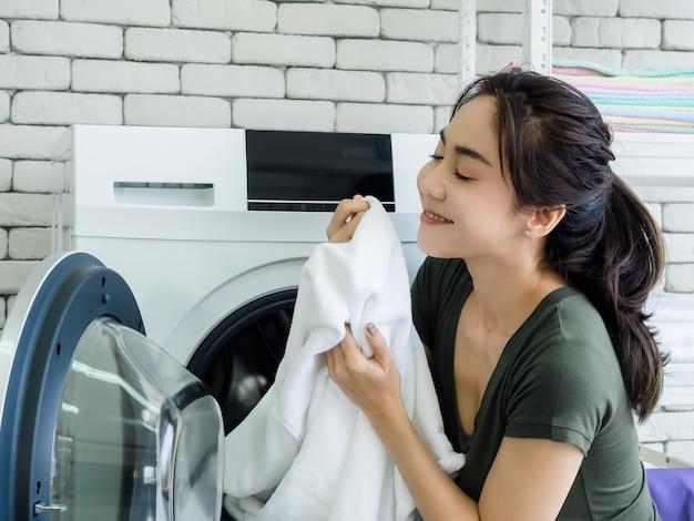 Крупным планом красивая молодая азиатская женщина-домохозяйка сидит с улыбкой и пахнущим белым чистым полотенцем после стирки из стиральной машины в прачечной.