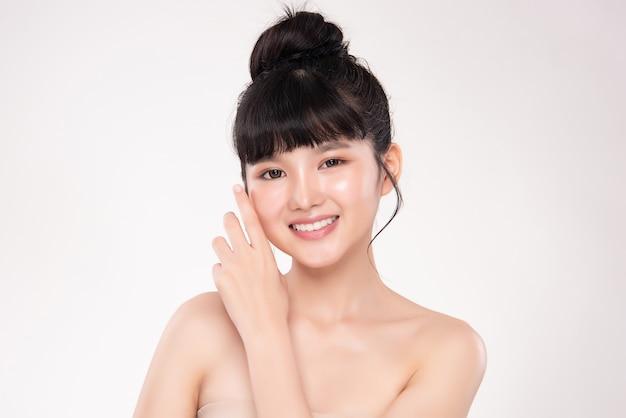 신선한 건강 한 피부 미용 화장품 및 페이셜 트리트먼트 개념으로 그녀의 깨끗한 얼굴을 만지고 아름다운 젊은 아시아 여성을 닫습니다