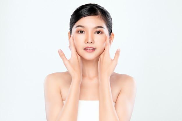 新鮮な健康な肌、分離、美容化粧品、フェイシャルトリートメントのコンセプトで彼女のきれいな顔に触れる美しい若いアジア女性を閉じる