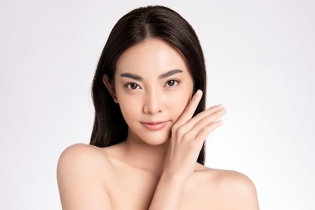 白い壁、美容化粧品、フェイシャルトリートメントのコンセプトに、新鮮な健康的な肌で彼女のきれいな顔に触れる美しい若いアジア女性を閉じる